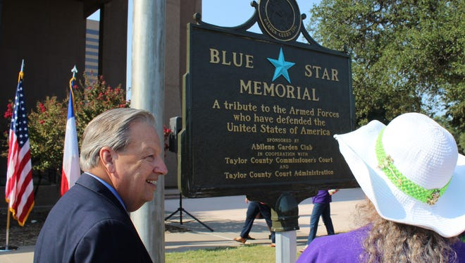 Taylor County Judge Downing Bolls talks to Abilene Garden Club member Karen Saunders after Monday morning's dedication of a Blue Star Memorial at the north side of the Taylor County Courthouse. The marker honors those who served in the U.S. Armed Forces.