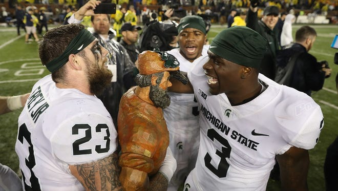 Michigan State's Chris Frey, left, and LJ Scott celebrate the 14-10 win over Michigan with the Paul Bunyan Trophy at Michigan Stadium on Oct. 7, 2017 in Ann Arbor.