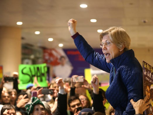 Warren speaks to a crown gathered at Logan Airport