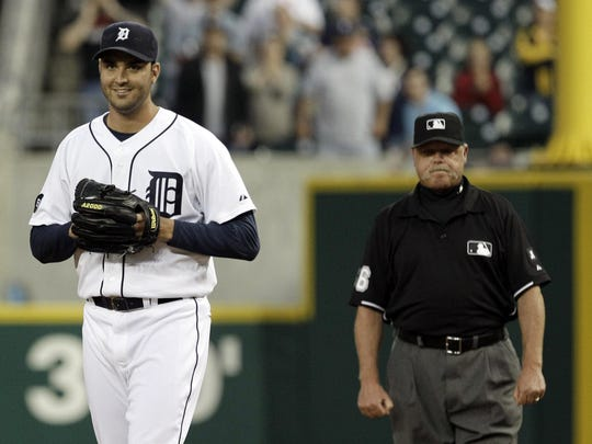 Detroit Tigers pitcher Armando Galarraga, left, smiles as he walks away from first base umpire Jim Joyce, right, who called Cleveland Indians' Jason Donald safe at first base to break up Galarraga's perfect game June 2, 2010.