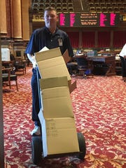 Randy Wallace, a custodian at the Iowa Capitol, wheels a load of paper - including some dead bills - toward a recycling bin. He says lawmakers are using far less paper today compared with a decade ago because of more reliance on electronic copies of legislation.