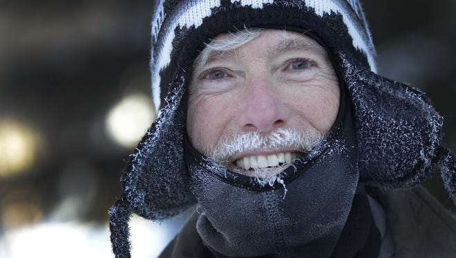Moisture turns to ice on the face of Dave Gerlach as he runs along North Center Street on Tuesday in Appleton.