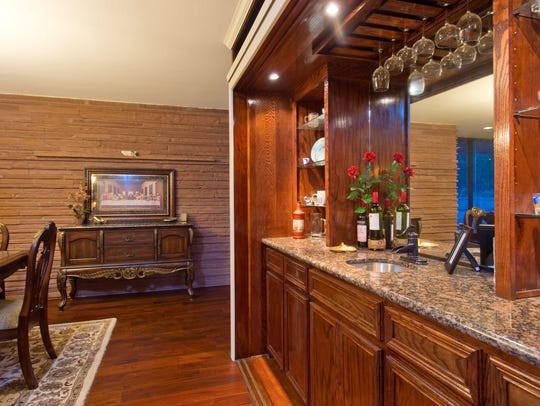 A built-in, granite-topped wet bar anchors the living