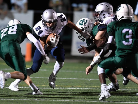 Andrew Word (24) attempts a run for Reitz against Owensboro Catholic in the Independence Bank Border Bowl played at Steele Stadium in Owensboro, August 25, 2017.
