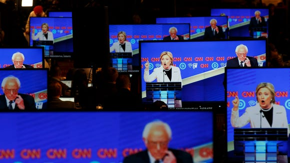 Hillary Clinton and Bernie Sanders are seen on television screens in the press room during a CNN-sponsored debate at the Brooklyn Navy Yard on April 14, 2016.