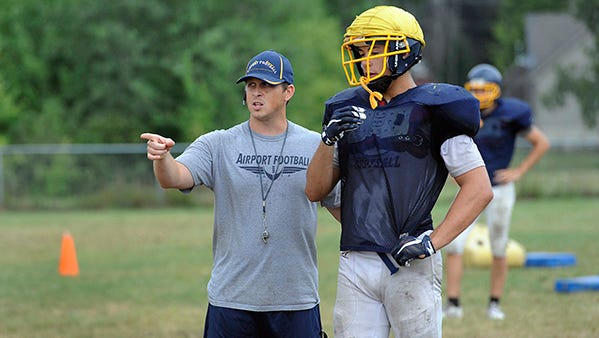 Carleton Airport head coach Chad Baas gives instructions to junior tight end/linebacker Brent Mossburg (6-foot-3, 210 pounds), who has offers from Ferris State and Davenport.