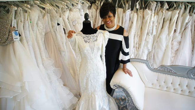 Monica Dudley, owner of Bella's YOUnique Bridal Boutique, stands next her wedding dress that she renewed her vows in 10 years after she married her husband of 37 years, Gerry.