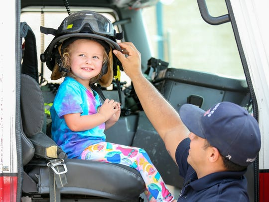 "Olivia Weir, 3, of Las Cruces, gets a tour the  Las Cruces Fire Department's Truck 1  on Saturday, July 29, 2017, during the Parks and Recreation Department's ""Kids EXPO 2017"" at the Plaza de Las Cruces. Placing the helmet on the girl's head is firefighter Steve Gonzales."