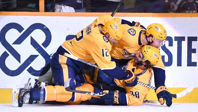 Predators right wing Ryan Hartman (38), center Mike Fisher (12) and right wing Miikka Salomaki (20) land on the ice after celebrating Hartman's empty-net goal late in the third  period in game 2 of the first round NHL Stanley Cup Playoffs at Bridgestone Arena Saturday, April 14, 2018, in Nashville, Tenn.