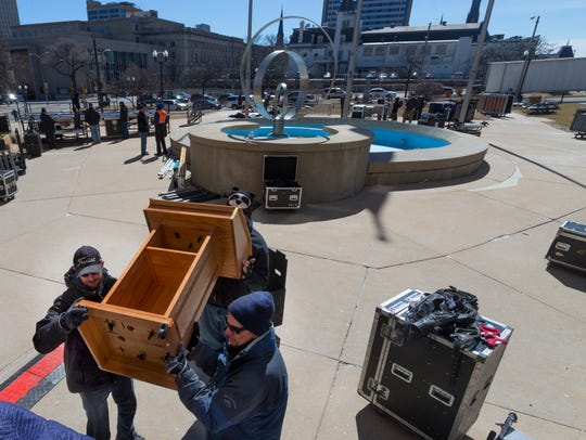 Workers move a podium into place in advance of the
