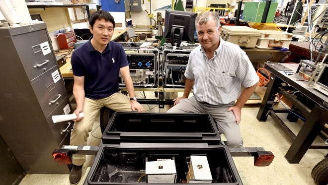 Professor Dryver Huston (right) and Associate Professor Tian Xia sit on a trailer-mounted ground-penetrating radar prototype they are building and testing at the UVM School of Engineering.