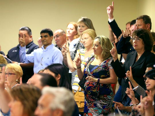 People raise their fingers after then-District Attorney Mark Skurka asked where people can start helping when it comes to domestic violence during the Coastal Bend Coordinated Community Response Coalition meeting Thursday, July 7, 2016, at First Baptist Church in Corpus Christi.