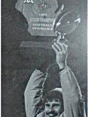 New Berlin Eisenhower coach Jeff Setz hoists the 1995 WIAA state football championship trophy after defeating Ashland, 7-6.