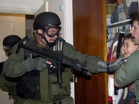 Fisherman Donato Dalrymple holds 6-year-old Elian Gonzalez inside a bedroom closet on April 22, 2000, as a Border Patrol agent tries to take the boy during a raid by federal agents.