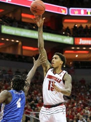 U of L's Ray Spalding (13) shoots against MTSU's James Hawthorne (4) during the NIT at the Yum Center in Louisville.    