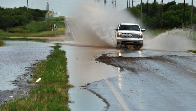A pickup truck passes through water flowing over the roadway on State Highway 258 near Farm-to-Market 368 Friday after the area received early morning heavy rain.