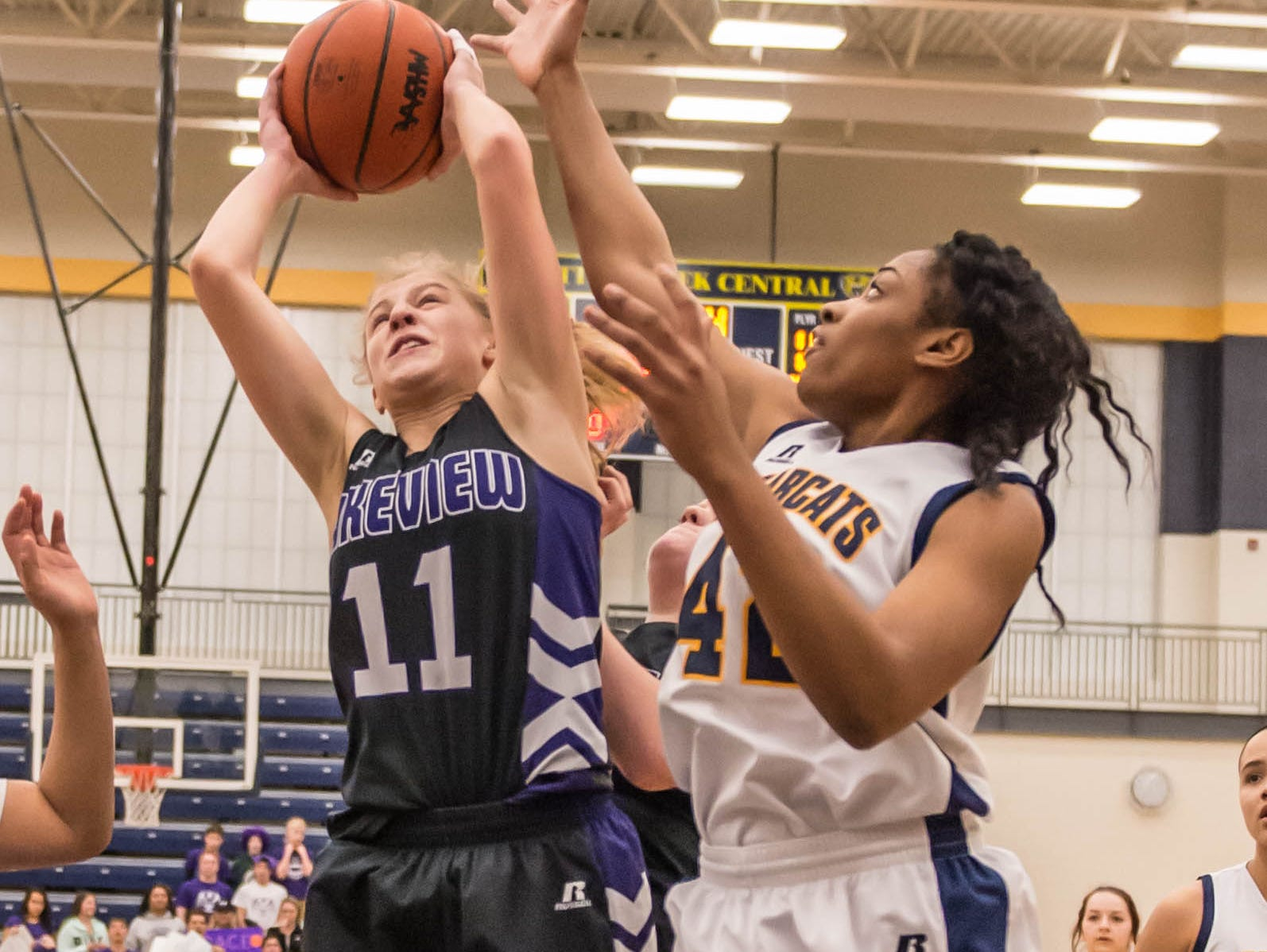Lakeview's Ava Cook (11) goes for the hoop while being guarded by Battle Creek Central's Jamesha Smith (42) during district finals Friday evening.