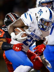 University of Memphis running back Doroland Dorceus (right) scores an 8-yard touchdown, his second against the University of Cincinnati defense, during second quarter action in Cincinnati.