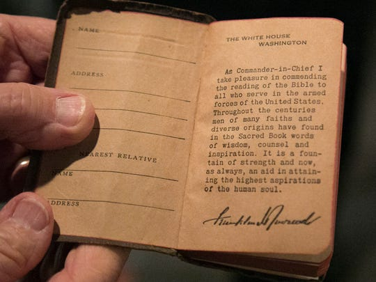AMVETS Post 26 chaplain Bill Loughman displays an intro to the New Testament written by President Franklin Delano Roosevelt for servicemen in World War II.