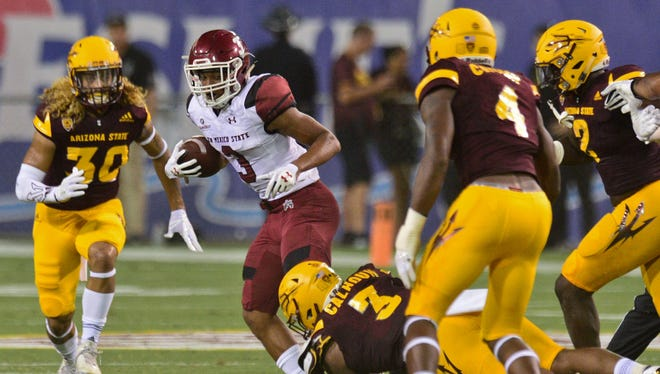 New Mexico State Aggies running back Larry Rose III (3) is tackled by Arizona State Sun Devils linebacker DJ Calhoun (3) during the first half at Sun Devil Stadium.