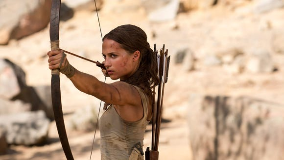As Lara Croft, Vikander shoots arrows, climbs rocks