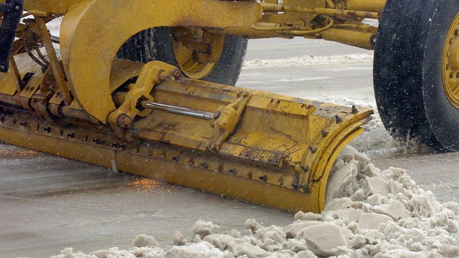 Sparks fly from the blade of a snowplow as it scrapes to the pavement while clearing streets.