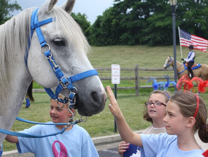 Ella Cooper, 9, of Union, pets the nose of a horse from the Young Guns equestrian drill team along with Mary Duncan, center, 8, of Verona and Peyton O'Bryan, 10, of Union, as the Union Celebrates America parade forms in parking lots off Braxton Drive Friday, June 27.