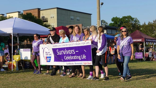 FSU's Relay for Life opening ceremonies ended and cancer survivors gathered to walk around the field as student organizations and booths cheered and clapped.