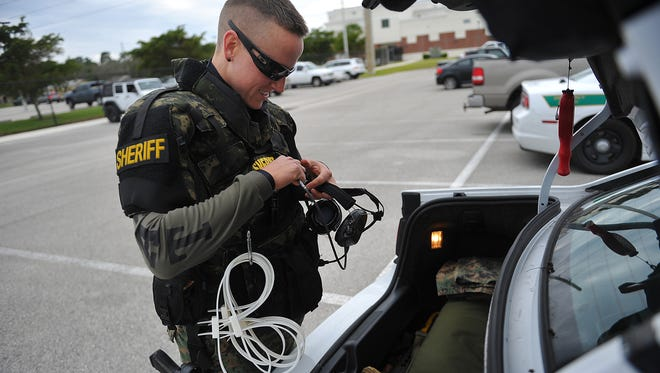 Indian River County Sheriff's Deputy Kelsey Zorc removes her protective gear after undergoing training at the Indian River State College's Treasure Coast Public Safety Training Complex on Nov. 19, 2014 in Fort Pierce.