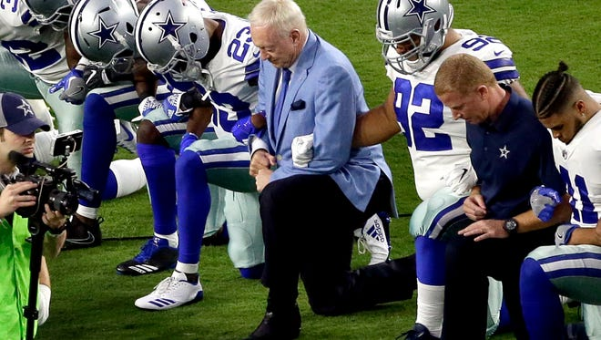 Dallas Cowboys owner Jerry Jones joins his players in taking a knee before Monday's game against Arizona.