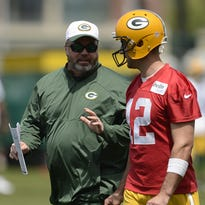 Green Bay Packers coach Mike McCarthy and quarterback Aaron Rodgers talk during organized team activities on June 2 at Clarke Hinkle Field.