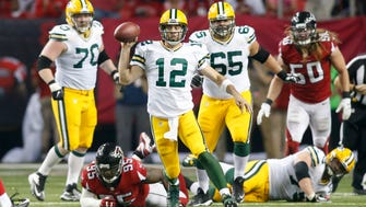 Green Bay Packers quarterback Aaron Rodgers (12) scrambles against the Atlanta Falcons in the fourth quarter at the Georgia Dome.
