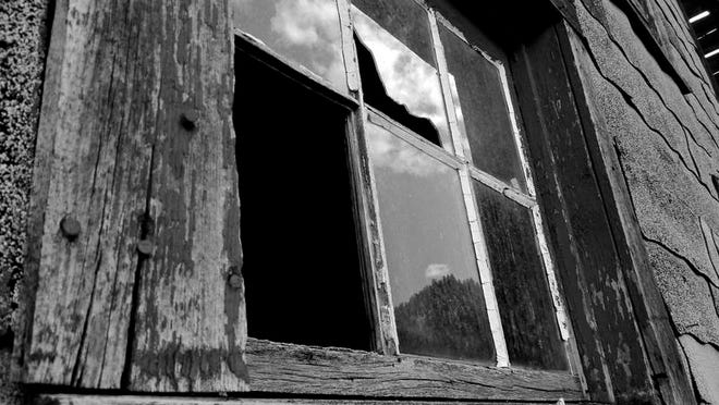 """Minica Casbara won the top prize in the youth category of the Tribune photo contest with this close-up of a window of an old, collapsing barn still in use in Boulder. """"I cropped this as much as I could without losing too much character,"""" Casbara said. """"I liked the reflection of the sky, clouds and mountain with trees, and how what is left of the broken pane kind of resembles an outline of the state."""""""