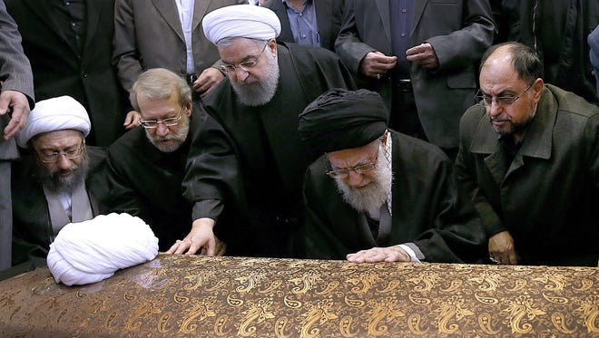 A handout photo made available by the Iranian Supreme leader official website shows Iranian supreme leader Ayatollah Ali Khamenei (2nd right) and Iranian president Hassan Rouhani (center) praying on the coffin of former Iranian President Akbar Hashemi Rafsanjani before his funeral ceremony in Tehran, Iran, Jan. 10, 2017.