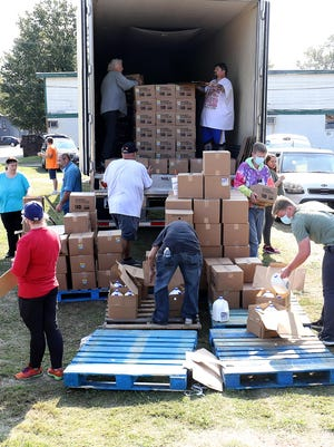 Volunteers with Pay It Forward - Fort Smith, distribute more than 40,000 pounds of USDA GoFresh produce, milk and chicken, Tuesday, Oct. 6, at the N. 10th and G St. food pantry.
