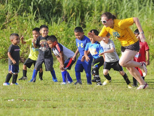Dededo Soccer Club coach Kelley Barnhart motivates the players in the under-6 division to warm-up before an afternoon of soccer practice next to at the Guam sports complex gym in Dededo on Aug. 18.