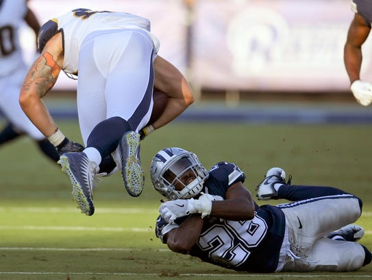 Cowboys defensive back Duke Thomas, bottom, tries to