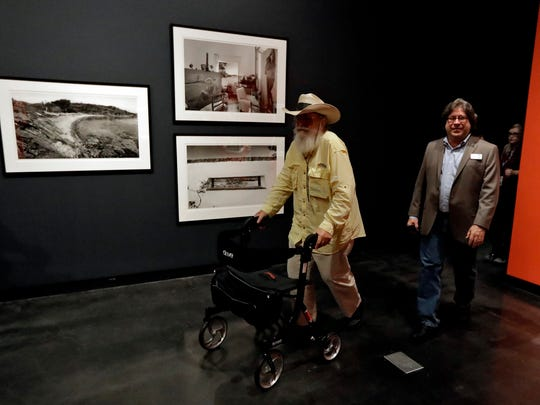"Clyde Butcher, left, and Peter Tush, Museum Curator of Education, enter a gallery during the opening of the ""Clyde Butcher, Visions of Dali's Spain"" exhibit, at the Salvador Dali Museum Friday, June 15, 2018, in St. Petersburg, Fla. The new exhibit features photographs of the places in Spain where Dali lived, shot by Butcher, a photographer renowned for his pictures of the Florida Everglades. (AP Photo/Chris O'Meara)"