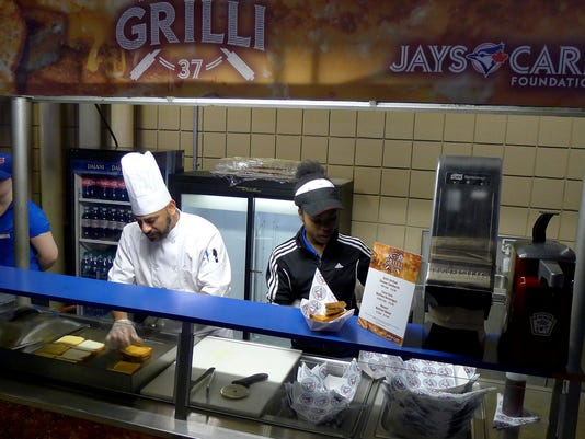 """People work at the Grilli sandwich counter at the Rogers Centre in Toronto on Wednesday, April 12, 2017. The Jays are running a """"Fire up the Grilli"""" promotion in April — which is also National Grilled Cheese Month — with a Jason Grilli-designed sandwich on sale at Section 244 of the Rogers Centre. A portion of the proceeds go to the Jays Care Foundation. (Neil Davidson/The Canadian Press via AP)"""