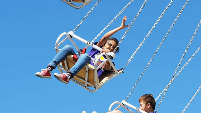 Flying high on the Phoenix, kids from the Boys and Girls Club enjoy the Rodeo Carnival on a special visit.