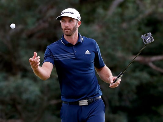 Dustin Johnson tosses his ball to his caddy on the 18th green during the final round of the Tournament of Champions golf event, Sunday, Jan. 7, 2018, at Kapalua Plantation Course in Kapalua, Hawaii. (AP Photo/Matt York)