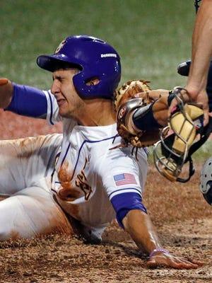 LSU's Brennan Breaux is tagged out by Rice catcher Hunter Kopycinski in the sixth inning of a college baseball regional tournament in Baton Rouge.