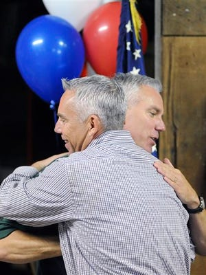 In this photo taken on May 31, 2013, Rob Snaza, right,  hugs his brother and Thurston County sheriff John Snaza, left,  during a meet and greet event at the Napavine Feed Store in Napavine, Wash. On Tuesday, Nov. 4, 2014,  Lewis County voters elected Rob Snaza to become the next sheriff, while John Snaza remains sheriff in neighboring Thurston County. (AP Photo/The Chronicle, Brandon Hansen)