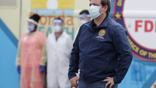 Florida Gov. Ron DeSantis wears a face mask as he listens during a news conference at a COVID-19 testing site at Hard Rock Stadium, during the new coronavirus pandemic, Wednesday, May 6, 2020, in Miami Gardens, Fla.