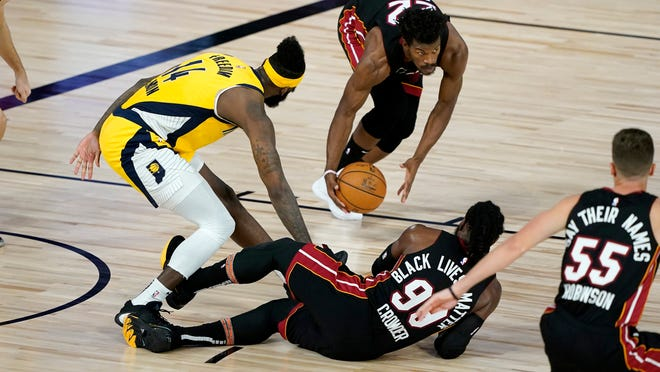 Miami Heat's Jimmy Butler picks up the loose ball as teammate Jae Crowder (99) and Indiana Pacers' JaKarr Sampson (14) battle for the ball during the first half of an NBA basketball first round playoff game, Thursday, Aug. 20, 2020, in Lake Buena Vista, Fla. (AP Photo/Ashley Landis, Pool)