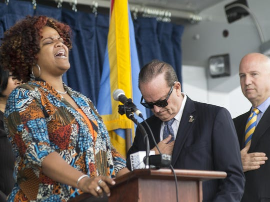 """Leonette Davis-Collins sings the """"Star Spangled Banner"""" as New Castle County Executive Tom Gordon and Governor Jack Markell look on. More than 100 people gathered Tuesday to celebrate the ground breaking of the $21 million library on Del. 9 south of Wilmington."""