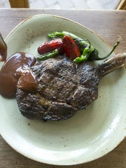 A cowboy ribeye steak with homemade steak sauce at