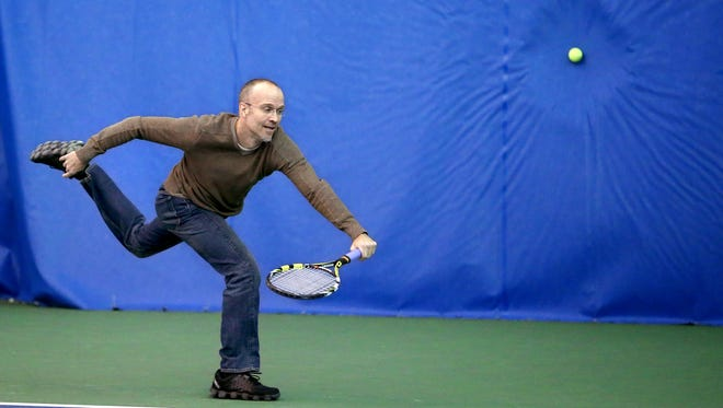 IndyStar sports columnist Gregg Doyel horribly misses a 120 mph or faster serve from Carmel tennis pro Rajeev Ram at the Five Seasons sports club in Indianapolis on Nov. 20, 2014.