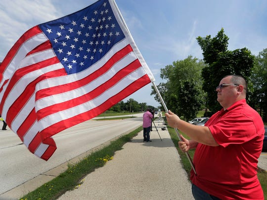 Timothy Nelson of Oak Creek waves a flag Saturday outside