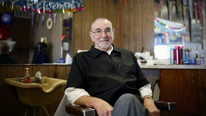 Hank Hall, who has been a barber for over 61 years, sits in his chair.